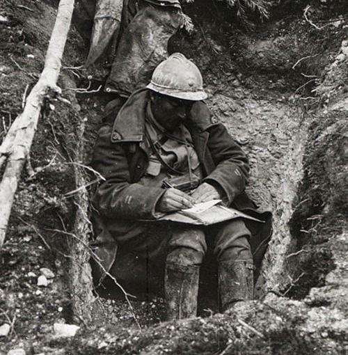Poilu écrivant dans une tranchée